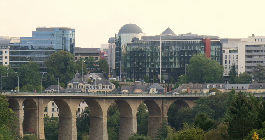 Panoramic cityscape, skyline view of business district with modern urban architecture of office tower buildings and old town bridge in front in the center of Luxembourg city, travel to Europe video