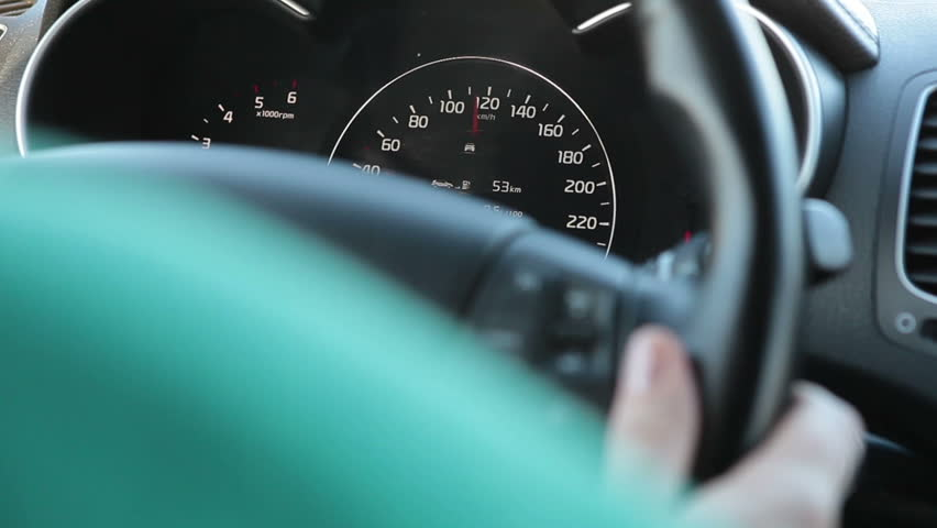 Car speedometer while driving about 100 km in hour, female hand steering wheel
