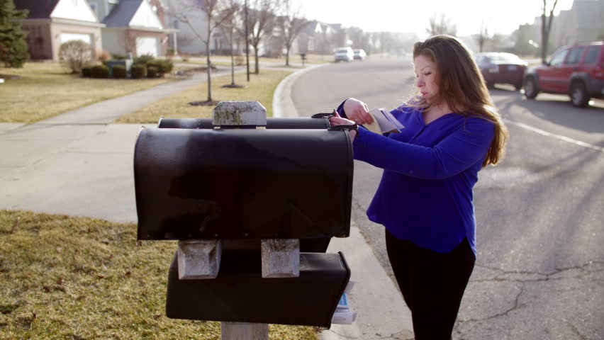 Brunette in blue sweater, collecting letters from her mailbox in a typical suburb of the USA's Mid West.  Early morning sunlight.  Hand held camera, looking down street, recorded in 4K.