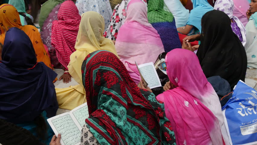 AJMER, INDIA - 30 OCTOBER 2014: Colorfully dressed women read verses during Muharram celebrations inside the Dargah shrine in Ajmer, India.