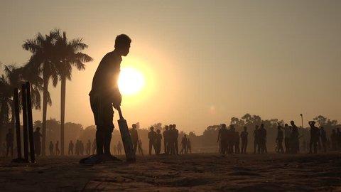 DHAKA, BANGLADESH - 19 DECEMBER 2014: Young men play cricket inside Ramna park at sunset, in Dhaka.