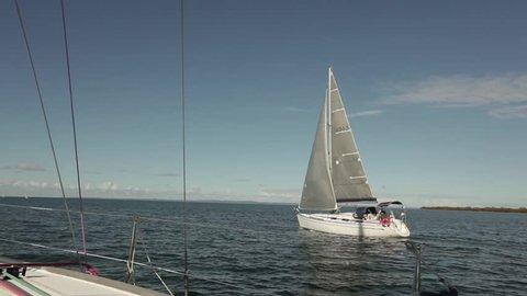 Medium shot of a sailing boat sailing by at sea - Sailing in Moreton Bay, Queensland, Australia