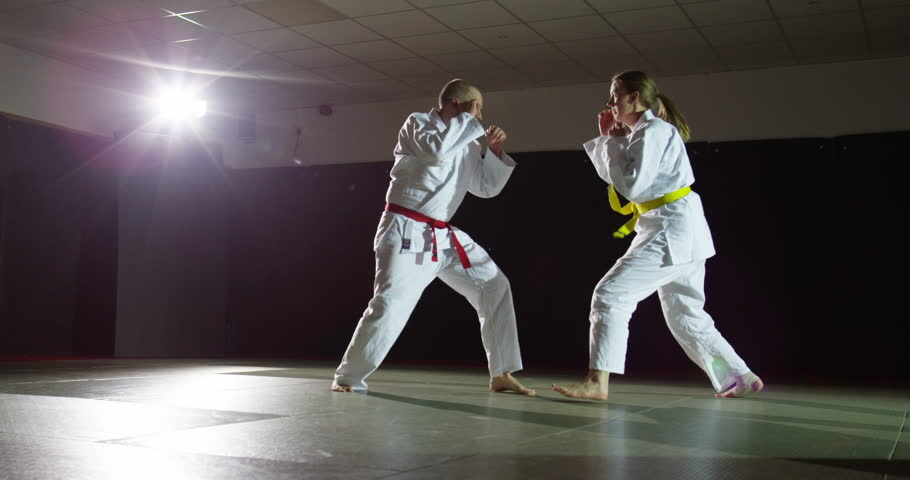 Two martial artists on a mat in slow motion