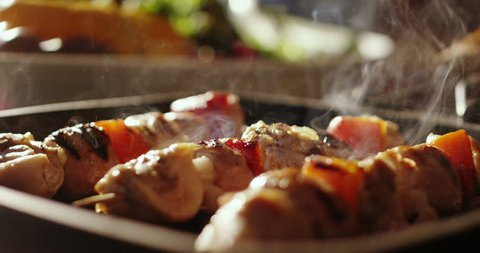 Super slow motion of skewers of meat with vegetables cooked on a spit in a pan (close up)