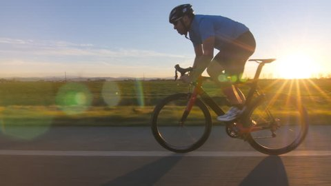 healthy man riding bicycle working out fitness outdoors at the sunset.  tracking shot 4k from camera car