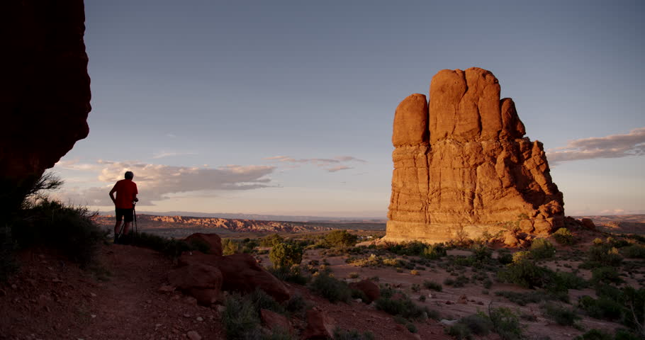 Arches National Park, Moab Utah.  Silhouetted Photographer taking photos of massive sandstone monolith at sunset.