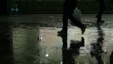 Slow motion silhouette of pedestrians walking on rainy pavement reflecting city illumination. Ginza, Tokyo.