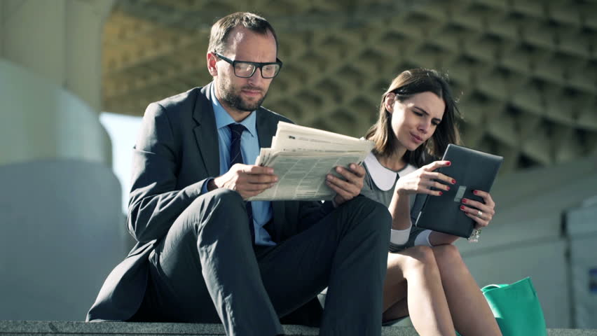 Businesspeople with newspaper and tablet computer sitting on stairs in the city