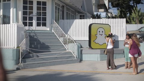 Venice Beach, California, USA – August 19, 2013: Three young women texting on their phones in from the SnapChat headquarters. Documentary Editorial.