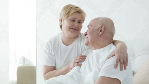 I love you. Happy smiling retired couple lying together in their bed hugging each other talking about different stuff