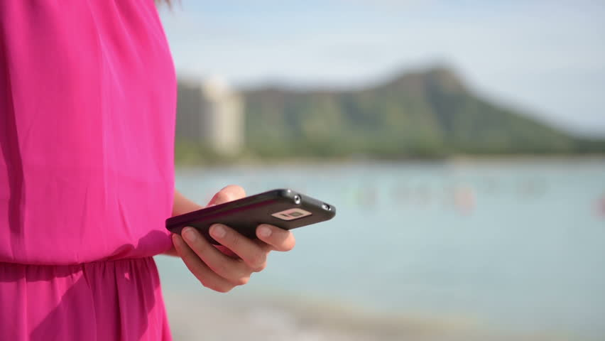 Close up of Woman Wearing Fuchsia Dress Holding Mobile Phone at the Beach. Girl Using Smartphone App on Smart phone Outside.   Shutterstock HD Video #9603857