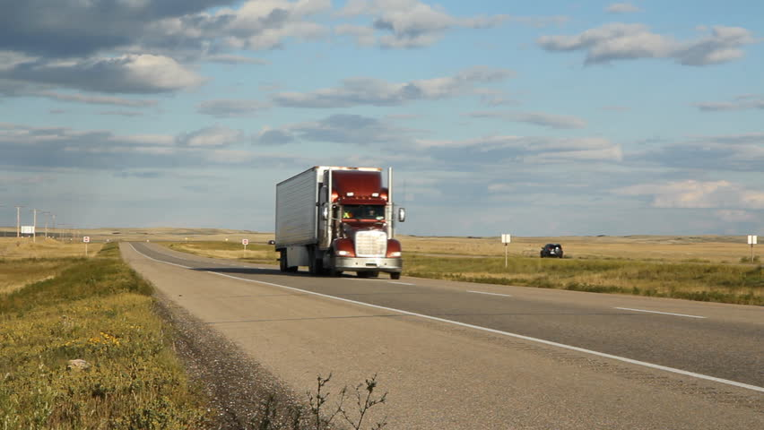 Red truck and car passing on the highway. Saskatchewan, Canada. Beautiful prairie landscape.