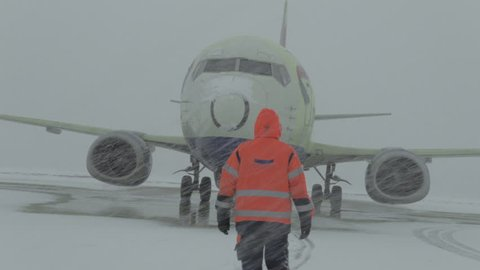 AUSTRIA, INNSBRUCK - FEBRUARY 10, 2012: Processing aircraft anti-icing, Winter storm, Airport traffic, landing airplanes,