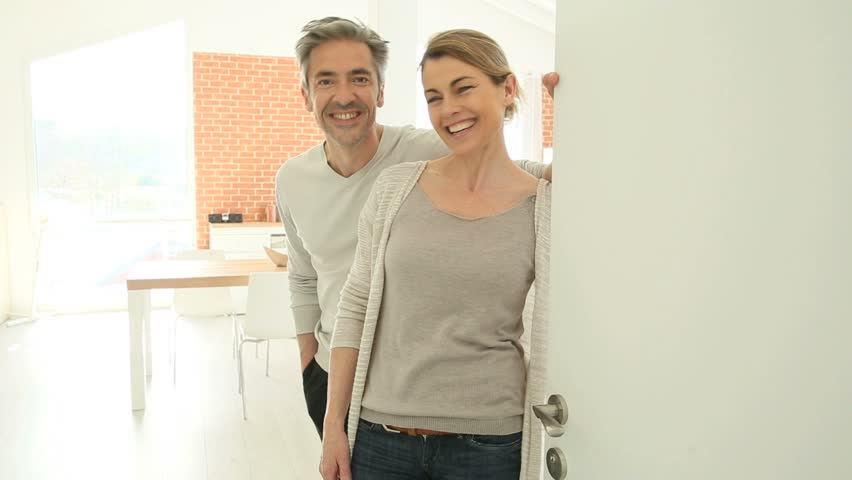 Couple opening house's front door to let people in | Shutterstock HD Video #9670277