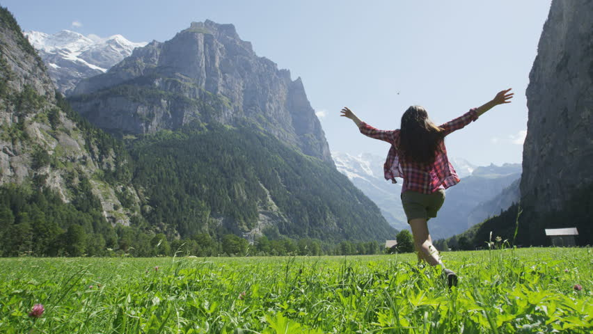 Happy woman having fun running in field nature excited of joy happiness. Joyful active lifestyle with free girl enjoying freedom, Lauterbrunnen valley, Swiss Alps, Switzerland. RED EPIC SLOW MOTION