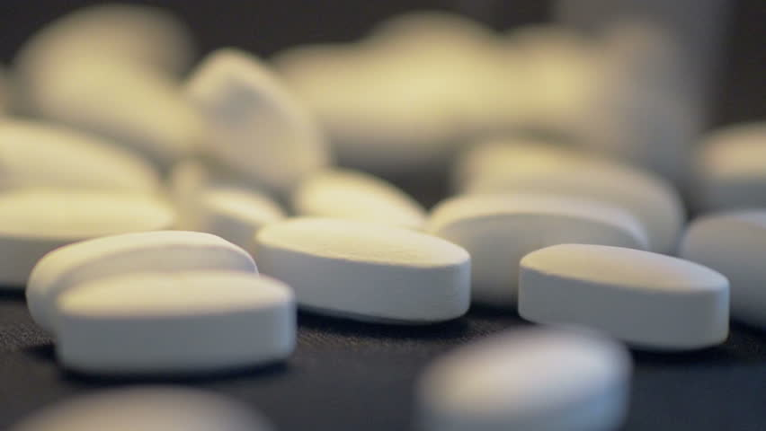 Spilling White Pills Close Up. A close up shot of spilling white pills. Great for medical, pharmaceutical, health care, senior related promotional materials and documentaries.