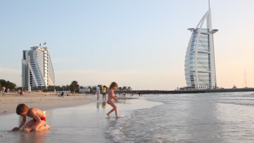 DUBAI - APRIL 17: Children playing on beach near Burj Al Arab, five-star hotel, at sunset on April 17, 2010 in Dubai, United Arab Emirates. At 321 m (1,053 ft), it is the fourth tallest hotel in the world