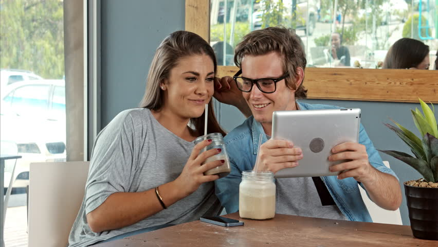 Wide shot of young couple using digital tablet computer in cafe. | Shutterstock HD Video #9733817