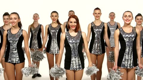 Beautiful dancing girls: cheerleading, pom-poms in hand, smiling at the camera, synchronous movement, girl waving their hands