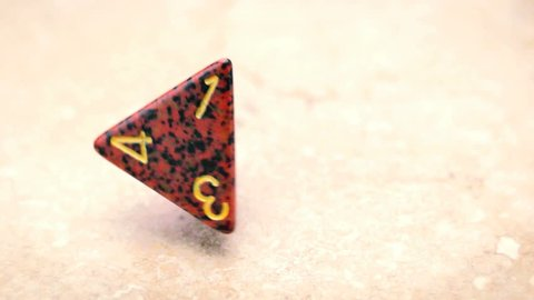 Four sided dice falling in slow motion, generic d4 role playing die