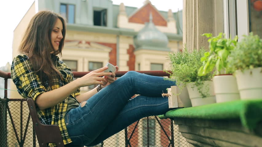 Girl sitting on balcony and have a videocall on the phone