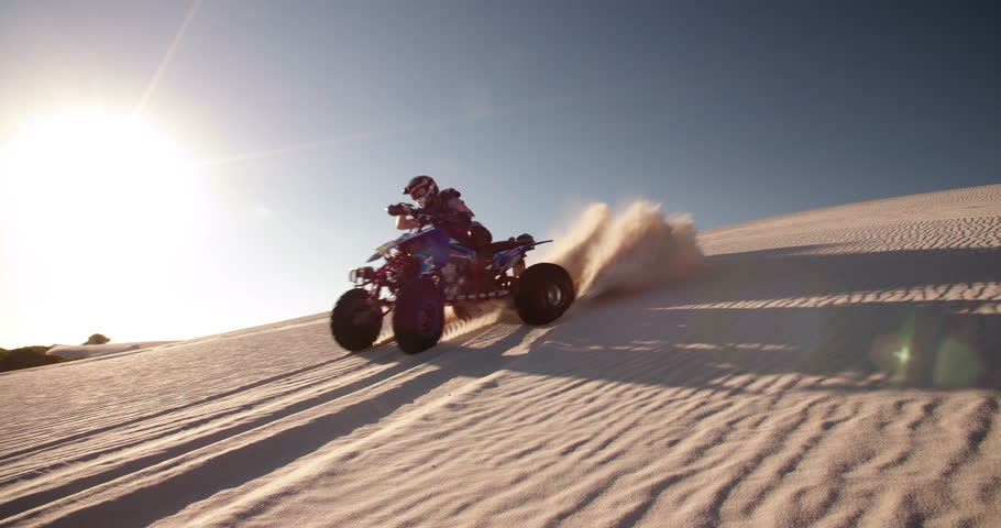 Competitive quad bike racer kicking up sand while driving up a sand dune on a summer evening with sun flare, Slow Motion, Panning #9774887