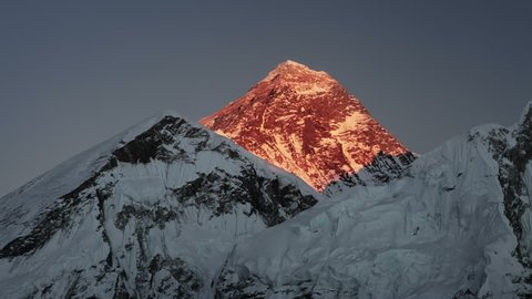 Time-lapse of Mount Everest at sunset. The sunlight on the peak and west face turns red and then fades to black.