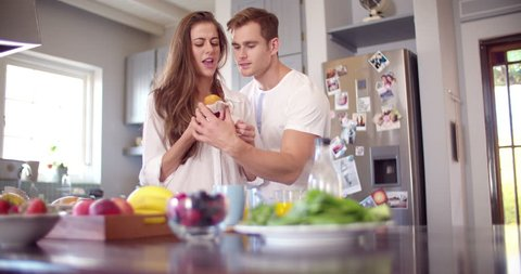 Cheeky boyfriend stealing a bite of his girlfriend's muffin in the kitchen early in the morning in Slow Motion