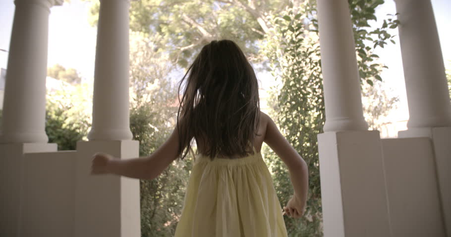 Rearview of a little girl running happily towards an open front door with vintage feel, Panning in Slow Motion