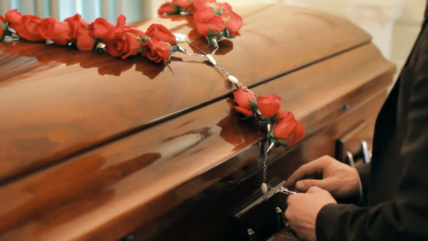 Coffin at funeral service or wake, person giving last respects to deceased