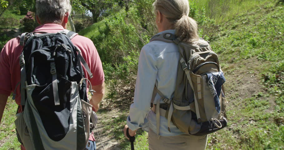 Active senior couple trekking on trail