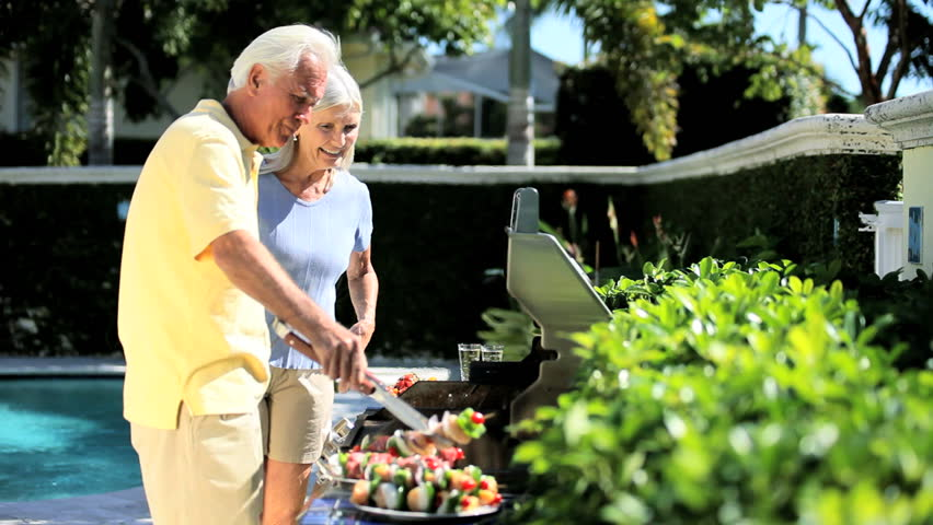 Senior couple enjoying healthy eating grilling food on a barbecue outdoors