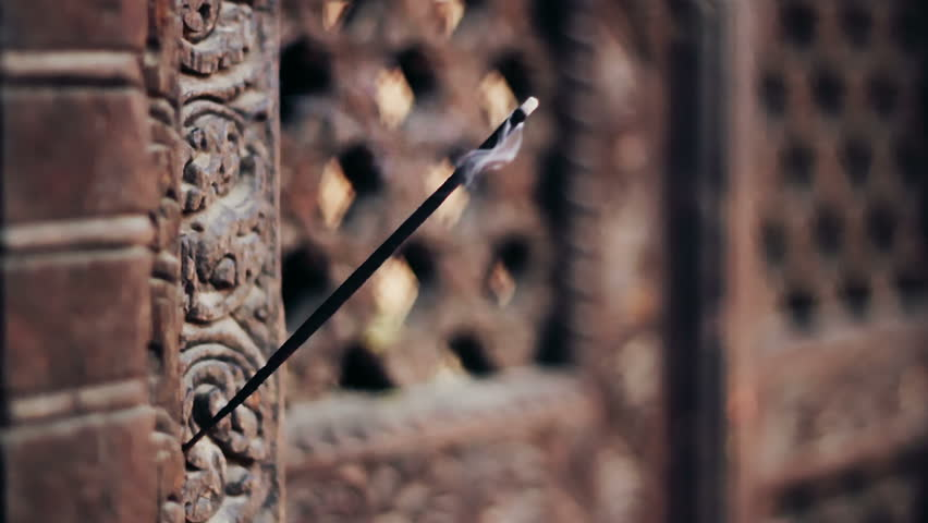 A burning incense stick placed on the intricate wooden carvings of the Pashupatinath (Yaksheswor Mahadev) Temple in Bhaktapur, Nepal. Bhaktapur is listed as World Heritage Site by UNESCO.