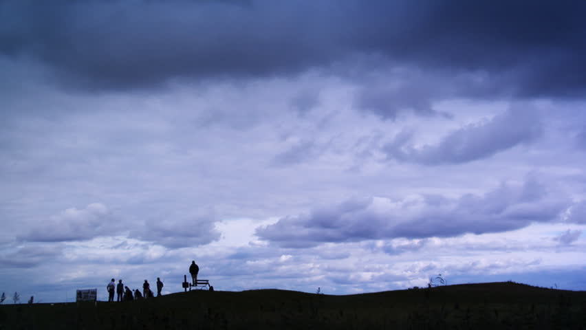 Cloudscape scenery over a golf course with golfers in the foreground