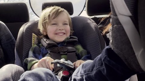 Closeup Of Little Boy Playing In His Car Seat, Excited To Go For A Drive