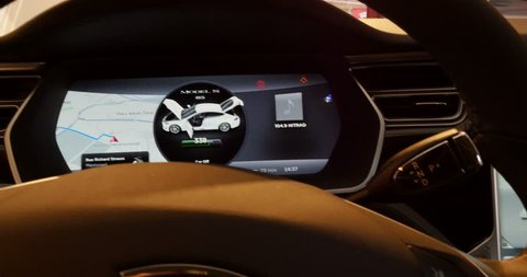 PARIS, FRANCE - CIRCA 2015: POV at Large LCD dashboard screen monitor with touchscreen capabilities of a Tesla Model S luxury car Tesla is an American company that designs, manufactures electric cars
