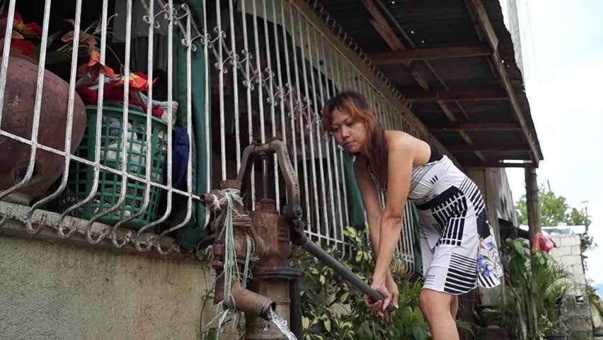 Beautiful lady pumps out water from a deep well hand held water pump