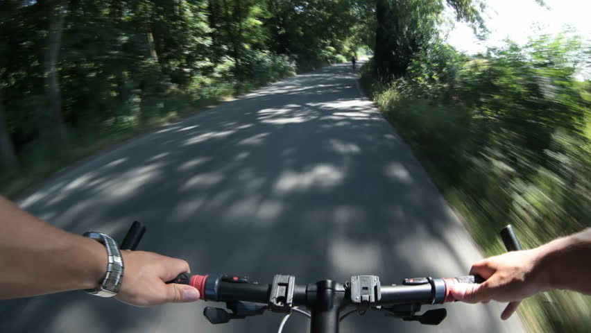 biking (riding a bike on a lovely sunny day;  motion blurred footage shot from a moving bike)
