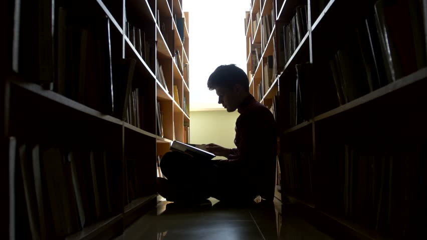 College student sitting on floor in library, reading book. Vertical shape, side view, full length, copy space | Shutterstock HD Video #9926705