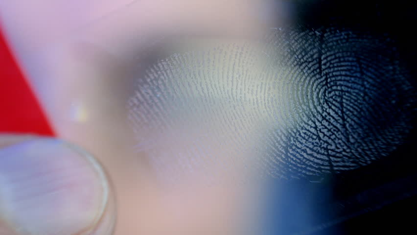 Investigator examines fingerprints on adhesive tape. Follow focus. Shallow depth of field