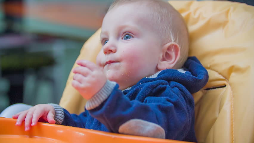 Blue Eyes Baby Seating Behind The Table. Young Baby Boy Seating In ...